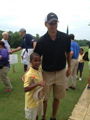 Stephen Curry takes a moment with First Tee participant Nicholas Terrell during a celebrity golf match to celebrate the organization's 10th anniversary and encourage local youth.