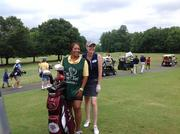 WCNC meteorologist Megan Danahey and her caddie, Rhoda Davenport, pause for the crowd during a celebrity golf match hosted by The First Tee of Charlotte, which is a youth program that teaches children about golf and life skills.