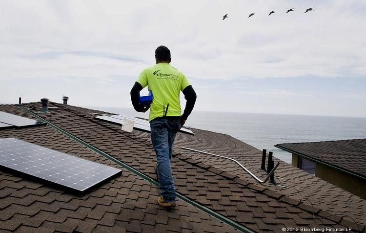 An installer prepares the roof of a home for solar panel installation in Encinitas, Calif.