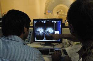 Aditya Singh, left, post-doctoral researcher for the University of Hawaii, and Will Alameida, chief operating officer at KinetiCor, review a scan in the MRI scanning room.