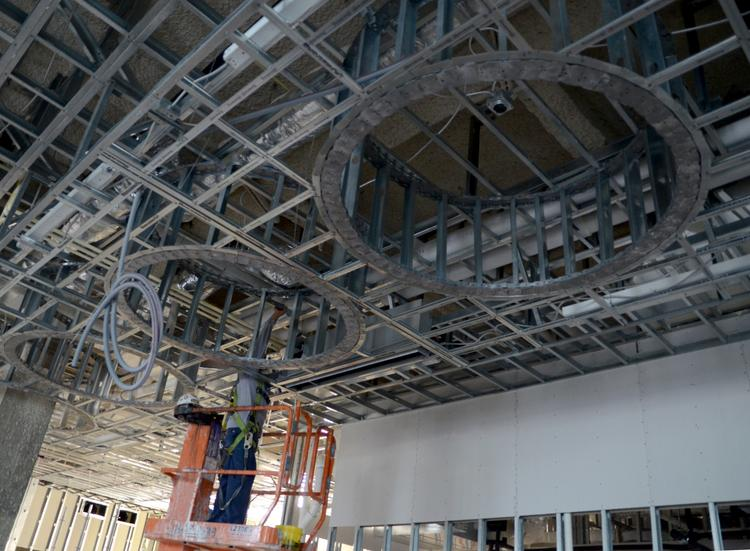 Work crews install wiring to ceiling features by the hotel bar at the Aloft Orlando Downtown.
