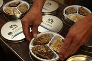 Toffee to Go's, Coby Taylor, production supervisor, breaks up toffee for a large order for USAA Tampa in special tins.