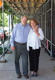 David Garrett, CEO of Garrett Hotel Consultants, and his wife, Christie. in front of the site of the Ivy hotel at the corner of N. Calvert St. and Biddle St.
