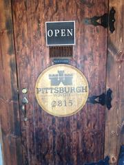 Sign on the wood door for the Pittsburgh Winery. Gaber said Pittsburgh Winery makes about 100 barrels each year.