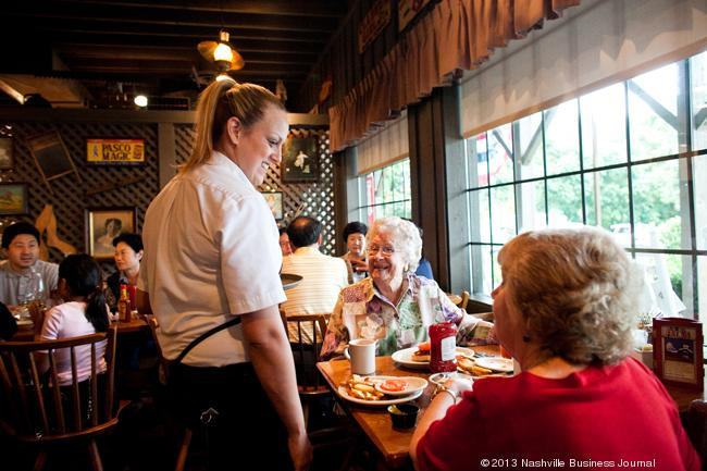 "Cracker Barrel waitress Kayla Clinton serves breakfast to Mildred Neely and her daughter Barbara Webb at the restaurant chain's Charlotte Avenue location. ""I have been known to come every day,"" Neely said."