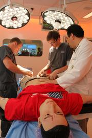 Dr. Luis Llerena, assistant professor of surgery at USF, and medical director of the Surgery & Interventional Training Center instructs Cole Giering and Bobby Rohrlack, both undergrad research assistants at USF, trauma OR. They are dealing with a double amputee mannequin due to an explosion.