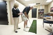 Robert Morrison practiced his putting at Baptist Health Louisville, while recreational therapist Susan Schildt steadied him.
