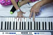 Brett Northrup, a certified music therapist, played an electronic keyboard alongside seven-year-old Meena Elgarmi recently for a therapy session in her Kosair Children's Hospital room.
