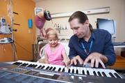 Brett Northrup, a certified music therapist, used an electronic keyboard with Meena Elgarmi recently as part of a therapy session in her Kosair Children's Hospital room. Meena is fighting cancer.