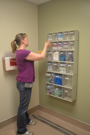 Megan McGhean, practice manager for OHSU Family Medicine at Richmond, stocks shelves at the new walk-in clinic.