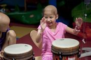 Meena Elgarmi, 7, seemed to enjoy beating the drums during a music therapy session at Kosair Children's Hospital. Lydia Haycraft, 7 watched Meena play.