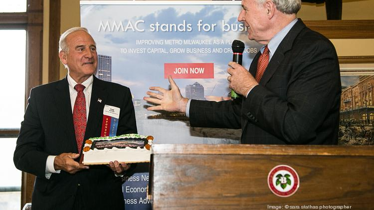 "Milwaukee Mayor Tom Barrett presents Metropolitan Milwaukee Association of Commerce chairman Ted Kellner a birthday cake during the MMAC's ""Madison Night in Milwaukee"" event Wednesday."