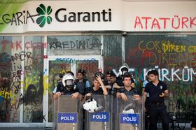 Turkish police stand behind riot shields outside a graffiti-damaged Turkiye Garanti Bankasi AS bank branch near Taksim Square in Istanbul on Tuesday, June 11, 2013. Turkish Prime Minister Recep Tayyip Erdogan's stand-off with protesters is threatening to send investor perceptions of the nation's credit risk above Russia's for the first time in seven months.