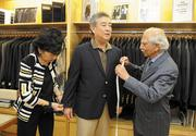 Alies and Andy Mohan measure customer Reid Nakamura for a suit.