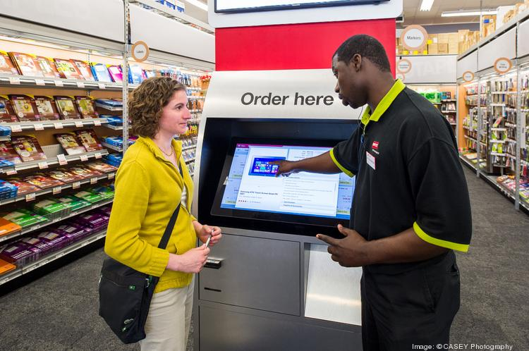 Customer Danielle D'Elia talks with Staples employee Kevin Kerr at the new Staples store in Norwood