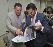 Jose Pazos of Pazos Robaina & Zapata Management Group and Ricky Patel of Farrell & Patel Attorneys at Law laugh about an image in the paper that makes it look like they are sharing Pazos' wife.