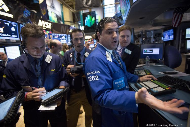 Traders work on the floor of the New York Stock Exchange in New York on Friday. U.S. stocks were little changed after the Standard & Poor's 500 Index reached a five-year high, and as Group of 20 finance chiefs met.