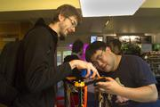 MAKING IT HAPPEN: Engineers Johann Rocholl (left) and Terence Tam share ideas on projects they are making with 3D printers at Metrix Create:Space. Tam currently has a Kickstarter project to mass produce 3D printer parts for the Openbeam Kossel Pro 3D printer which he developed at Metrix Create:Space.