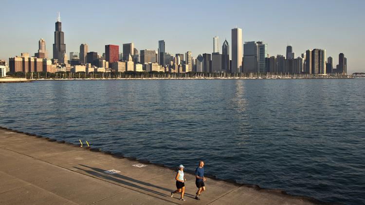 Runners jog along the shore of Lake Michigan in Chicago.