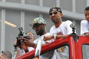 LeBron James wears a hat with a crown and a palm tree design. Next to him is Juwan Howard, who is the Heat's elder statesman when it comes to players.