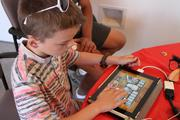 """A young fan tries his hand at the """"Whack-A-Ninja"""" mini-game in Kung Fu Robot."""