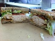 The No Ordinary Club sandwich features roasted chicken, avocado, bacon, lettuce, tomatoes, spicy mayonnaise on toasted multigrain bread.