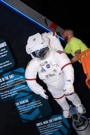 Some adjustments are made to a space suit, hanging above one of the displays.