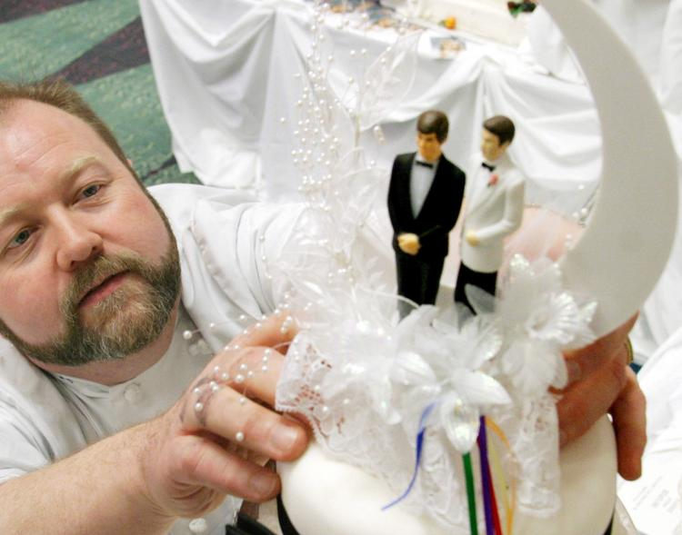 A baker adjusts a pair of same sex cake toppers.