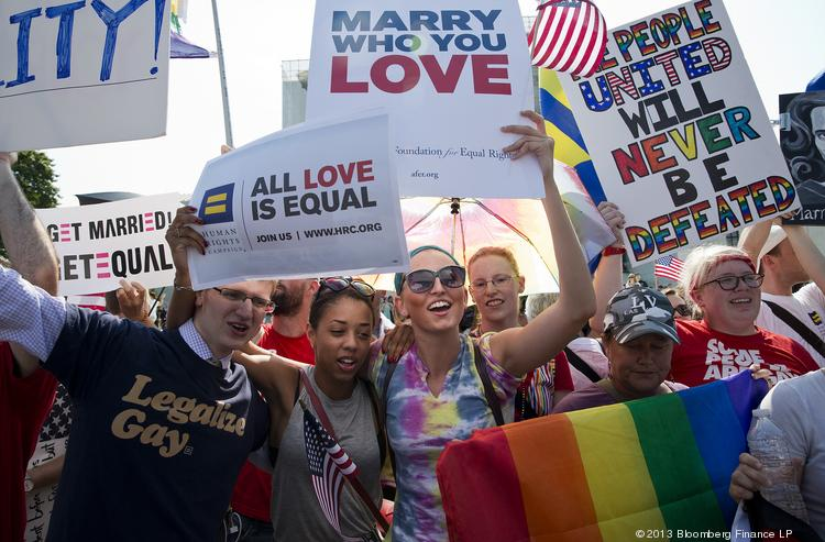 Supporters of gay marriage celebrate after the U.S. Supreme Court overturned the Defense of Marriage Act (DOMA) and declined to rule on the California law Proposition 8 in Washington, D.C., U.S. on Wednesday, June 26, 2013. A divided U.S. Supreme Court gave a landmark victory to the gay-rights movement, striking down a federal law that denies benefits to same-sex married couples and clearing the way for weddings to resume in California. Photographer: Joshua Roberts/Bloomberg