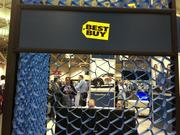 Conference attendees watch a TV at Best Buy's booth