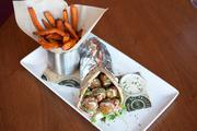 The edamame falafel pita, with shaved lettuce, red onion, tomato, cucumber, lemon-tahini dressing and frites is one vegetarian options for $13.
