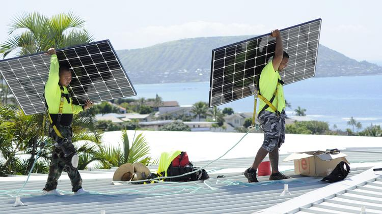 PV installers for Hawaii Energy Connection are seen in this file photo. The number of solar photovoltaic permits issued by the City and County of Honolulu in April fell 51 percent from the number issued in the same month last year.