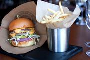 The Grille Prime Cheeseburger comes served with two parries, lettuce, tomato, fries, pickels and sloppy sauce for $15.
