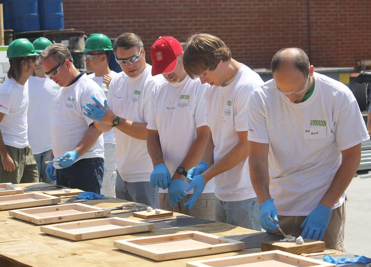 Students from UNC Charlotte work with volunteers from Ingersoll-Rand to make tiles for a solar-powered house.