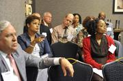 Janelle Rayford (left, in denim jacket) of Elevation Construction Group, asks a question during a breakout session.