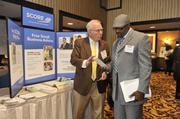Exhibitor Chuck Sawicki of SCORE speaks with  attendee Eugene Gregory of Gregory Arts Services.