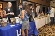 Elizabeth Henderson (left) of the McColl School of Business speaks with an attendee.