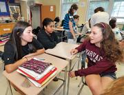Marina Angelopoulos speaks with classmates Isabelle Jaquith, left, and Taylor Terry, center, in their 8th grade social studies class at Van Antwerp Middle School.