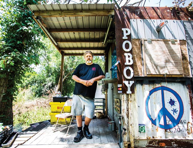 Ralph Gilmore shows his Turf & Surf Po-Boy food trailer, which used to be a staple at the corner of Congress Avenue and Second Street. It's being stored in an automobile body shop in East Austin, while his business has moved to a brick-and-mortar location on Lavaca Street.