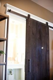 A door made of reclaimed wood with a custom slide fabrication.