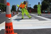 City of Milwaukee workers apply some paint for a unique design at the crosswalk near Cathedral Square in downtown Milwaukee.