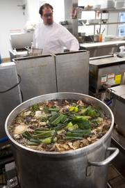 A stock pot simmers in the foreground as chef Ryan Montgomery works in the background at Charr'd.