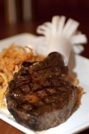 A 64-day dry-aged ribeye steak, served with Onion straws at Charr'd Bourbon Kitchen and Lounge.