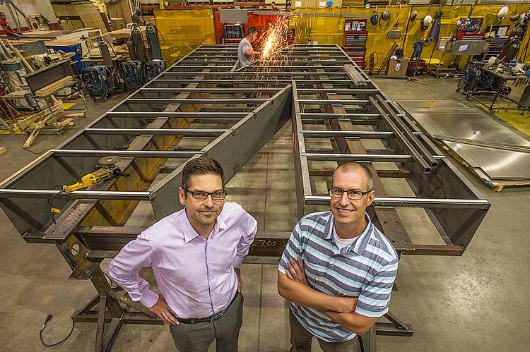"""Stephen Hopkins, director of innovation (left), and Tucker Trotter, president of Dimensional Innovations, stand in front of a large """"N"""" for a consultancy project they developed with the city of Lincoln, Neb."""