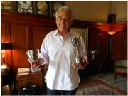 Business leader and philanthropist Michael Malone in his Seattle offices at Hunter Capital, with some of the trophies he won by racing vintage cars all over the world.