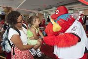 Kendal Strickland, left, holds daughter Akyla, 3, and they greet Reds mascot Gapper.