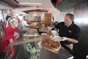 Sarah Smith, 13, gets a slice of LaRosa's pizza from Todd Hicks, event coordinator for LaRosa's.