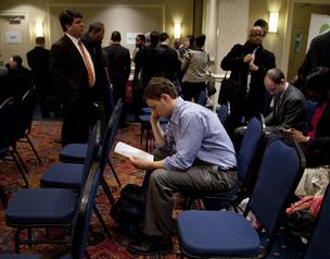 A job seeker looks over his resume before seeing recruiters at a job fair in New York.