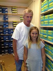 Bob Cocco, owner of Broadway Shoes, with his 10-year-old granddaughter, Rose Denue, who was helping him stock boxes of shoes to prepare for next week's opening.