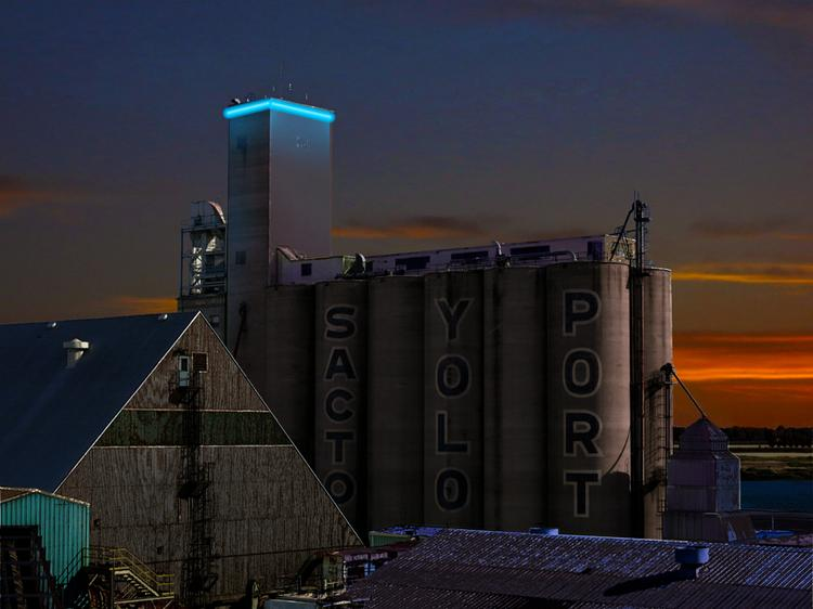 A blue light illuminates a grain tower at the port in West Sacramento. SSA Pacific is taking over port operations.